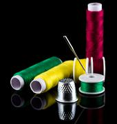 sewing thread needle and thimble - stock photo