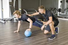 Fitness coach giving advice to trainee - stock photo