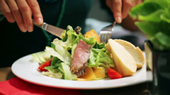 Woman eating salad at the restaurant, closeup, steadycam shot Stock Footage