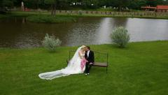 The bride and groom sit on the bench of the old homestead. Shoot camera crane Stock Footage