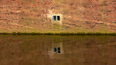 Brick wall and current river water in  sunlight Stock Footage