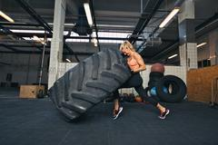 Crossfit woman flipping a huge tire at gym Kuvituskuvat