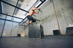 fit woman is performing box jumps at gym - stock photo