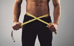 fitness man measuring his waist - stock photo