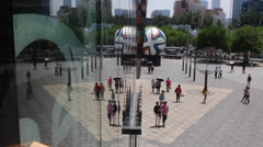 Time Lapse:People walking in front of a sculpture of the Brazuca soccer ball Stock Footage