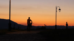 Father rotate little child at sunset, man and kid sihouette Stock Footage