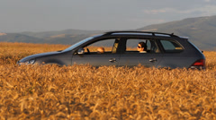 Little child driver and young mother in golden wheat land Stock Footage
