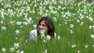 Stock Video Footage of Beautiful smiling woman lie down in daffodils field, long hair, flowers 4K