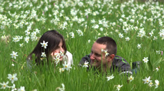 Lovely couple together in beautiful daffodils field, smiling to each other 4K Stock Footage