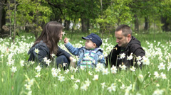 Perfect family, child offering daffodils to parents, enjoy flower fragrance Stock Footage
