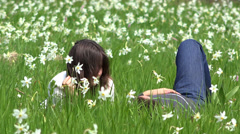 Romantic couple relaxing in blossom field, gentle daffodils swaying  Stock Footage