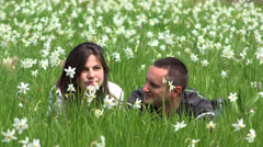 Young wife and husband relax in beautiful nature, daffodils field, keep the love Stock Footage