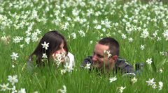 Lovely couple together in beautiful daffodils field, smiling to each other Stock Footage