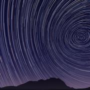 beautiful star trail image during at night - stock illustration