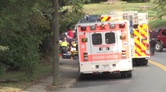 Rescue personnel tend injured as officer directs traffic  Stock Footage