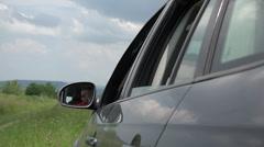 Lovely boy hanging head on car window waving hand sensing kisses, rural road 4K - stock footage