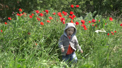Happy boy jump  in blossom field giving thump up Stock Footage