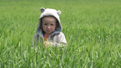 Funny little boy with mouse costume in green grain, lovely pest Stock Footage