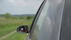 Lovely boy hanging head on car window waving hand sensing kisses, rural road - stock footage