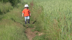 Little boy walking on village path,  difficult stepping 4K Stock Footage