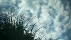Rain ripples on water surface with cloudy sky reflection Stock Footage