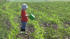 Lovely little baby playing with a sprinkler, try to wet the plants Stock Footage