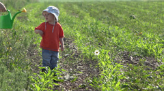 Little baby and mother hand holding a sprinkler irrigating together the flower Stock Footage