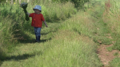 Lovely little boy walking on rustic path hold big flowers bouquet, innocent gift - stock footage