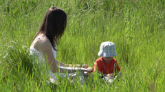 Little boy and young mother enjoy picnic on green park, healthy lifestyle Stock Footage