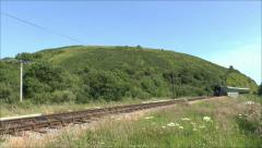 Steam train on the Swanage Railway passing close to Corfe Castle, Dorset, UK. Stock Footage