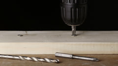 Drilling a screw out and into a wooden block on black background Stock Footage
