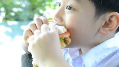 Little asian boy eating hamburger . Stock Footage