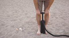 Man Using Air Pump on Sandy Beach Stock Footage