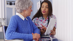Hispanic caregiver talking with tablet with elderly patient - stock footage