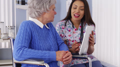 Stock Video Footage of Cheerful Mexican caregiver talking to elderly patient with tablet