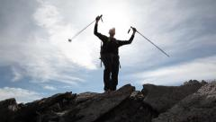 Hiker summits alpine ridge Stock Footage