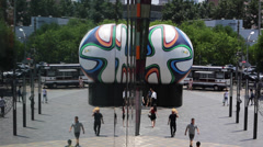 People walking in front of a sculpture of the Brazuca soccer ball Stock Footage