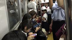 Using smartphones on Tokyo metro commute - stock footage