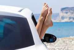 Woman's legs dangling out a car window Stock Photos