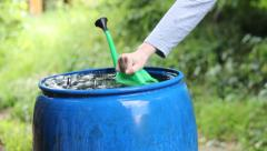 Woman takes rainwater from a blue barrel to watering garden Stock Footage
