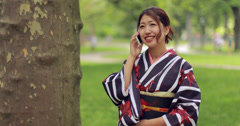 Young Asian woman talking cellphone in a park 4k - stock footage