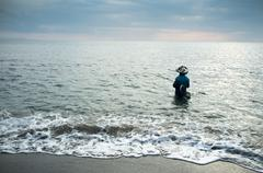Local fisherman standing in the sea, holding a fishing rod to catch fish, lom Stock Photos