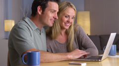 Happy couple looking for a vacation getaway on laptop Stock Footage