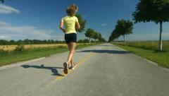 Woman jogging on road in spring Stock Footage