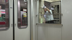 Tokyo metro employee at the rear of a train car Stock Footage