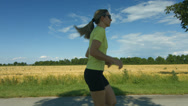 Stock Video Footage of woman running beside field