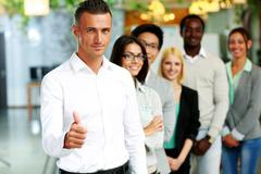businessman giving thumb up to camera in front of colleagues - stock photo