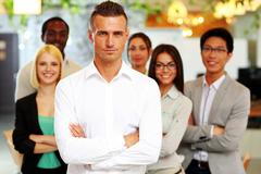 Stock Photo of handsome businessman with arms folded standing in front his colleagues