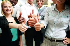 Cheerful business group giving thumbs up Stock Photos