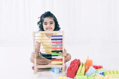Portrait of a girl playing with abacus and smiling Stock Photos